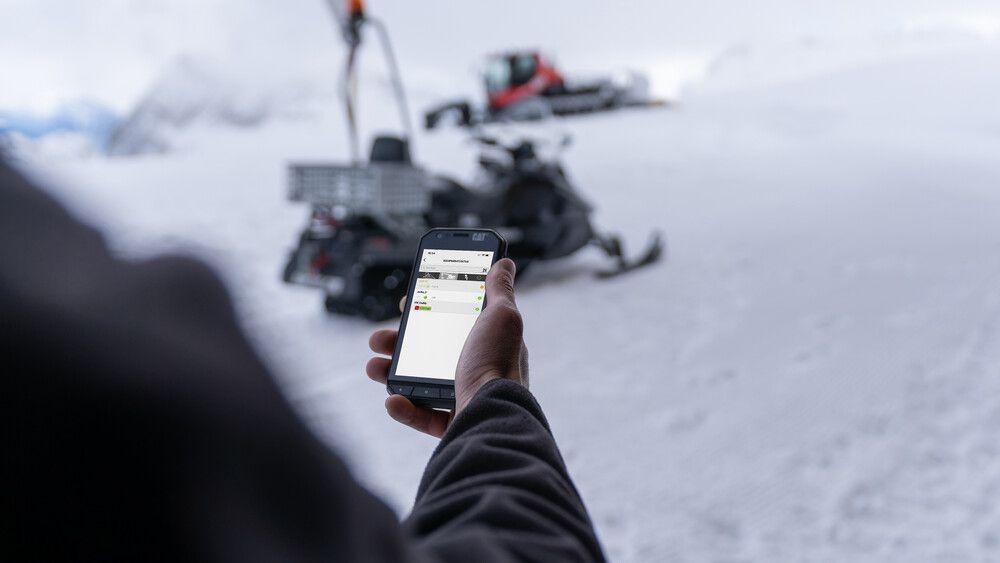 Eine Person bedient SNOWsat Maintain am Smartphone auf der Piste.