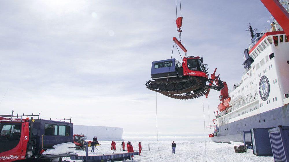 Ein PistenBully wird mit einem Kran vom Schiff auf das ewige Eis der Antarktis gehoben