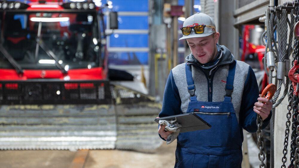 Eine Person bedient SNOWsat Maintain in der Werkstatt.