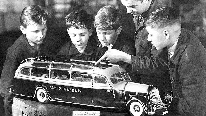 Vier Jungen lassen sich interessiert ein Modell des Alpen-Express erklären