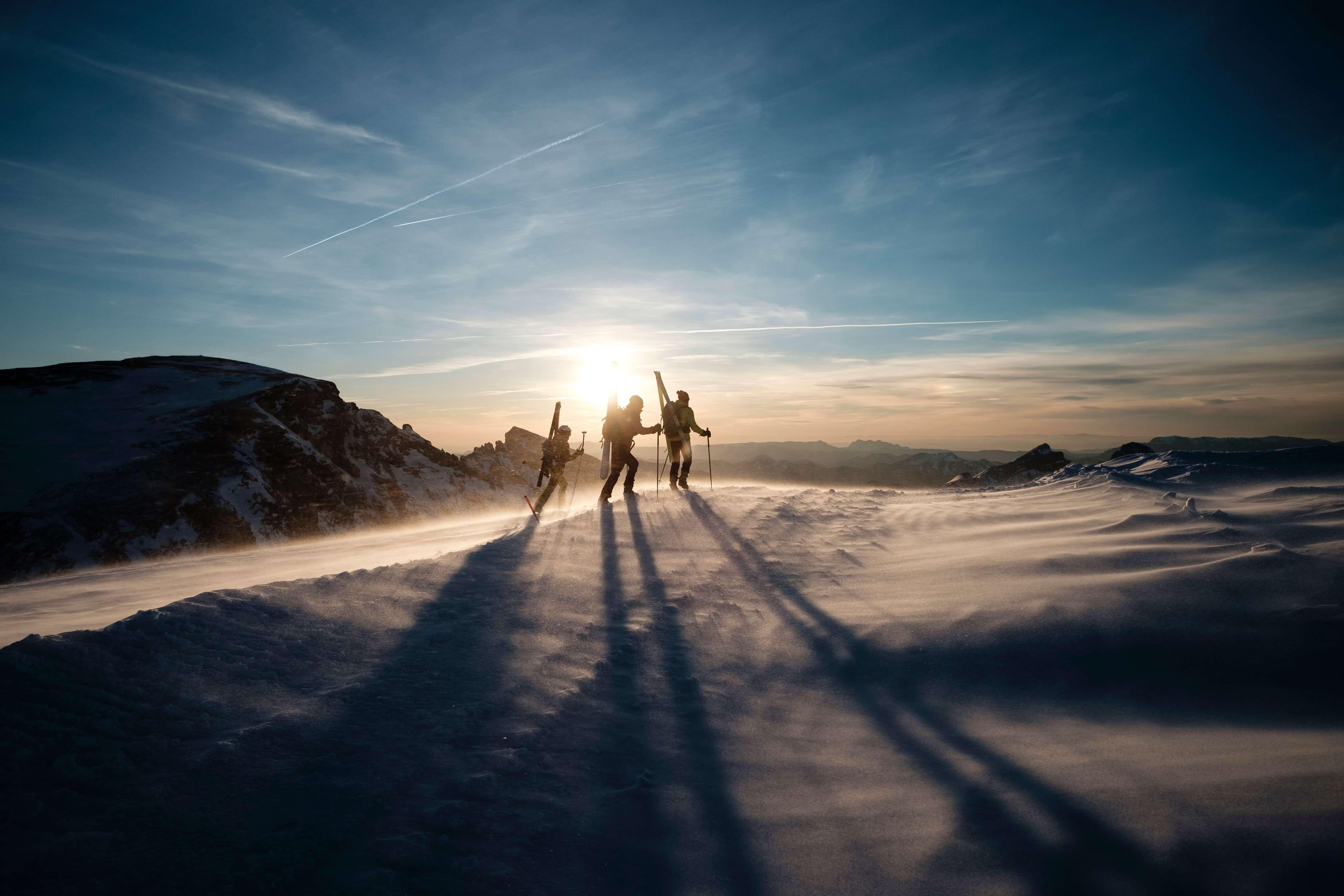 Tres escaladores escalan un pico bajo el sol de la mañana.