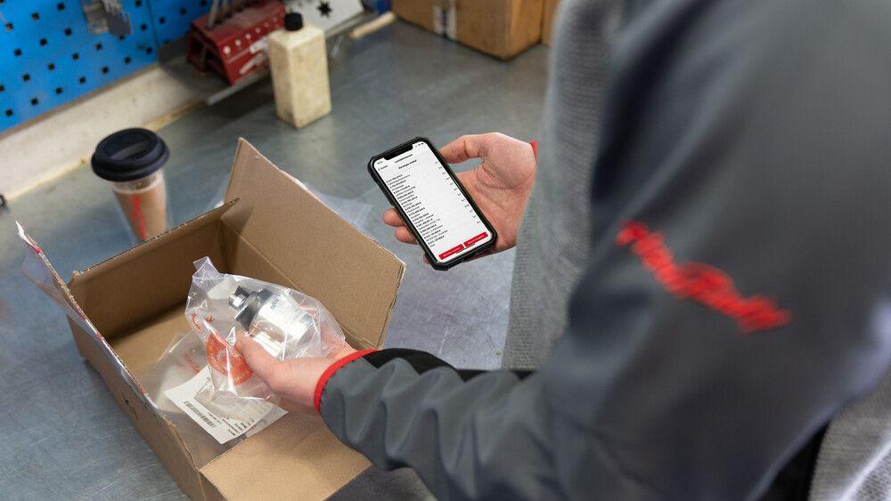 Eine Person bedient SNOWsat Maintain am Smartphone.