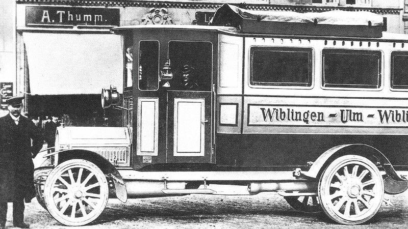 Karl Heinrich Kässbohrer steht stolz neben dem ersten Omnibus, der Wiblingen und Ulm verbindet